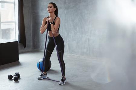Ejercicio físico. Mujer de deportes haciendo ejercicio con banda de resistencia en ropa de moda, entrenamiento de bucle. Alta resolución Foto de archivo