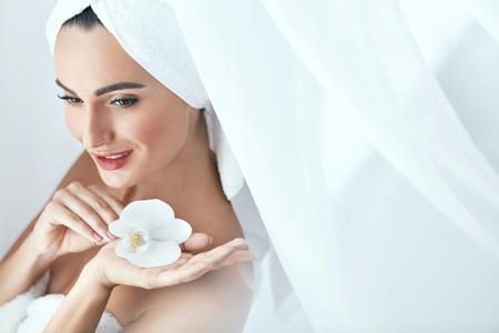 Schoonheidssalon. Vrouw In Handdoek Na Lichaamsverzorging Met Orchideebloem. Hoge resolutie