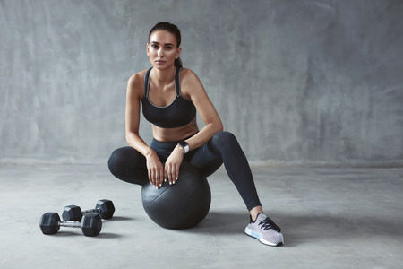 Sports Woman In Fashion Sportswear Sitting On Fitness Ball, Female In Stylish Sport Wear. High Resolution Stock fotó
