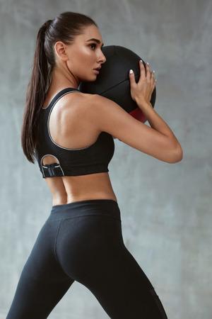 Sport donna formazione in moda abbigliamento sportivo nero, allenamento con palla fitness su sfondo grigio. Alta risoluzione