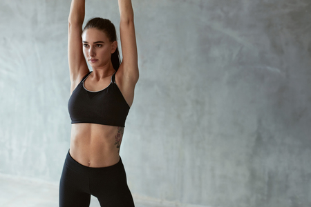 Sportfrau in der Mode Sportkleidung, die Körper vor dem Training auf grauem Hintergrund streckt. Hohe Auflösung Standard-Bild
