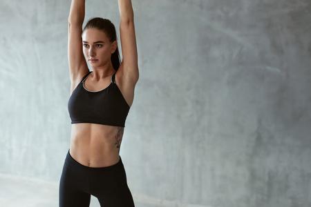 Sportvrouw In Manier Sportkleren Die Lichaam vóór Training op Grijze Achtergrond uitrekken. Hoge resolutie Stockfoto