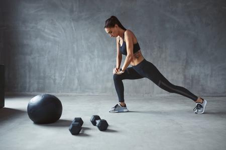 Esercizio. Donna di sport In abbigliamento sportivo di moda che allunga le gambe, formazione. Alta risoluzione Archivio Fotografico