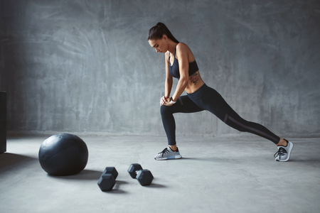 Oefening. Sport vrouw in mode sportkleding benen strekken, opleiding. Hoge resolutie Stockfoto
