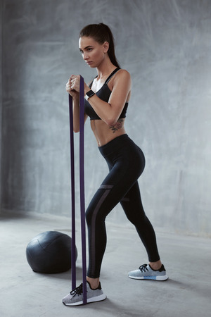 Fitness Exercise. Sports Woman Exercising With  Resistance Band In Fashion Clothes, Loop Workout. High Resolution
