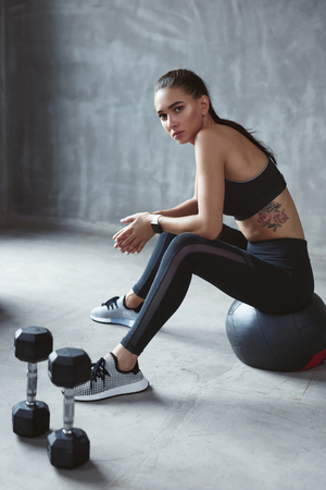 Woman In Black Stylish Sports Wear Sitting On Fitness Ball, Fitness Training In Grey Interior. High Resolution Reklamní fotografie