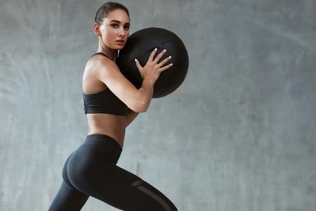 Sportfrauentraining in der Mode Black Sportswear, Training mit Fitnessball auf grauem Hintergrund. Hohe Auflösung Standard-Bild