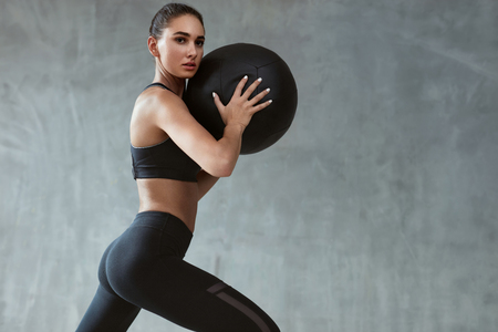 Sports Woman Training In Fashion Black Sportswear, Workout With Fitness Ball On Grey Background. High Resolution Stock Photo