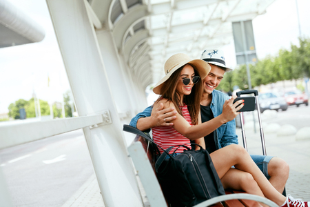 Travel. Couple Taking Photos On Phone Sitting At Bus Stop Near Airport Outdoors. Young People Traveling In Summer. High Resolution Standard-Bild