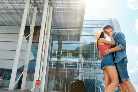 People Hugging In Airport. Loving Young Couple Embracing, Say Goodbye Near Departure Terminal. High Resolution