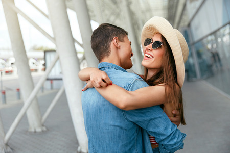 Traveling Couple Embracing In Airport. Happy Smiling People Hugging, Meeting After Long Time. High Resolution Stock Photo