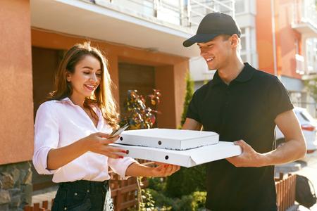 Livraison de pizzas. Courier donnant des boîtes de femme avec de la nourriture à l'extérieur. Commande de réception du client. Haute résolution