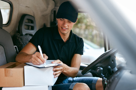 Delivery Courier In Car With Boxes. Man Delivering Packaging, Filling Delivery Document. High Resolution