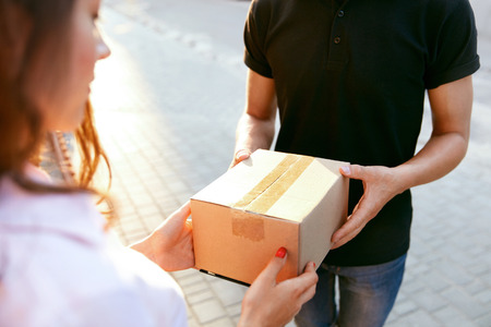Courier Delivery Service. Closeup Of Woman's Hands Receiving Package From Delivery Man. High Resolution Banque d'images