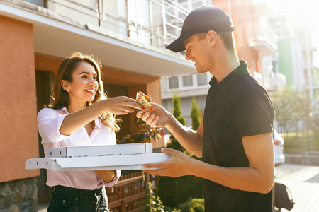 Food Delivery. Courier Delivering Pizza To Client Home. Woman Paying Order Outdoors. High Resolution