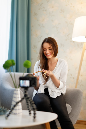 Fashion Blogger Filming Video On Camera At Home. Beautiful Woman Recording Vlog About Accessories Indoors. High Resolution Imagens