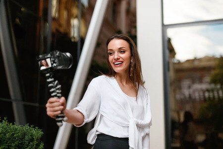Video Blogging. Woman With Camera Outdoors. Beautiful Smiling Female Filming Vlog Near Modern Business Building On Street. High Resolution