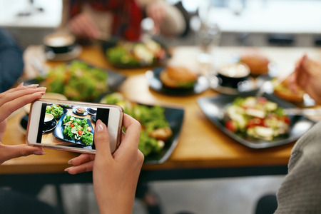 Photo On Phone. Closeup Woman Hands Photographing Food On Mobile Phone In Restaurant. High Resolution Stock Photo