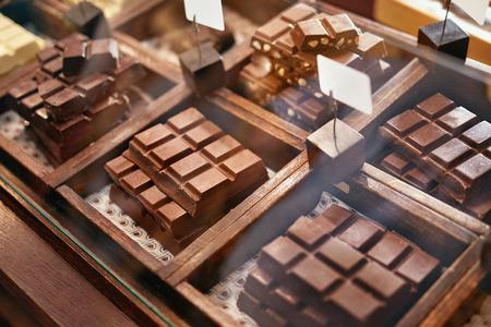 Barras de chocolate en el primer de la tienda de confitería. Chocolate artesanal en vitrina de madera en el taller. Alta resolución