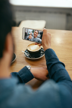 Online Video Call. Close Up Man Calling Using Phone. Closeup Of Male Hand Holding Mobile Phone With Man's Face On Screen. High Resolution