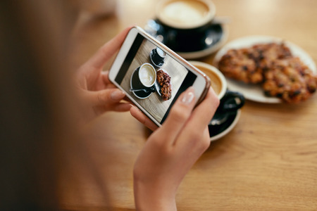 Food Photo On Mobile Phone In Cafe. Woman Hands Making Photos Of Coffee On Smartphone In Restaurant. High Resolution Banco de Imagens