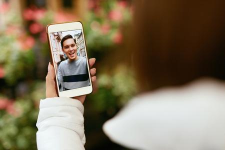 Videollamada en el teléfono. Cerrar la mano con el teléfono y la cara en la pantalla. Mujer llamando al hombre a través del chat de video en línea. Alta resolución