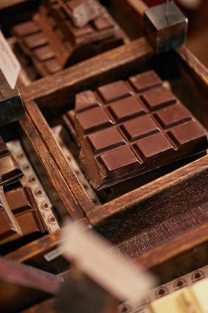 Chocoladerepen In Zoetwaren Winkel Close-up. Handgemaakte Chocolade Op Houten Showcase In Werkplaats. Hoge resolutie