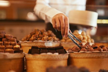 Pralinen im Süßwarenladen. Nahaufnahme der weiblichen Hand mit Pinzette, die Süßigkeit wählt. Hohe Auflösung