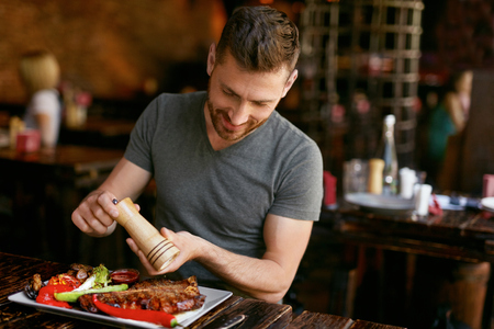 Man Eating Barbecue Meat With Vegetables In Grill Restaurant. Man Salting Cooked Steak. High Resolution