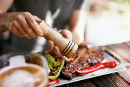 Man Eating Grill Meat With Vegetables Closeup. Male Hands Salting Barbecue Steak In Restaurant. High Resolution Stock Photo