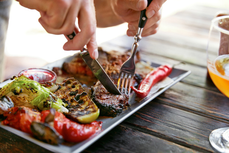 Eating Food. Close Up Man Eating Steak With Vegetables In Restaurant. Male Hands Cutting Grilled Meat With Knife And Fork. High Resolution Stock Photo