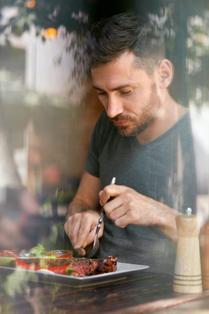 Restaurant. Man Eating Food With Beer At Cafe. Male Eats Barbecue Steak With Grill Vegetables. High Resolution Stock Photo