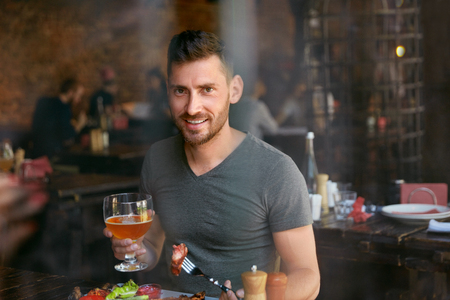 Man Drinking Craft Beer And Eating Steak In Restaurant. Male Having Dinner In Steak House. High Resolution Stock Photo