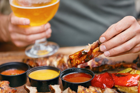 Eating Barbecue Food With Beer. Grilled Ribs With Sauсes Closeup. Man Hand Holding Pork Ribs. High Resolution