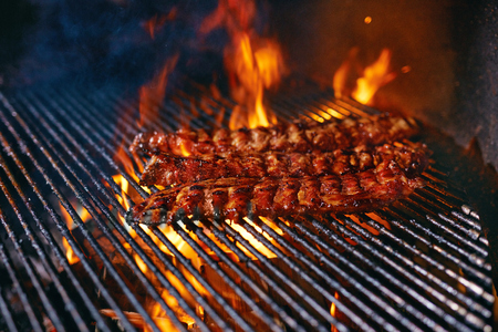 Pork Ribs Cooking On Grill Closeup. Cooking Grilling Meat On Fire. High Resolution Banco de Imagens - 108465129