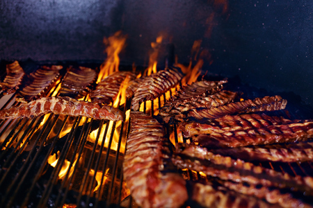 Pork Ribs Cooking On Grill Closeup. Cooking Grilling Meat On Fire. High Resolution Banco de Imagens - 108465130