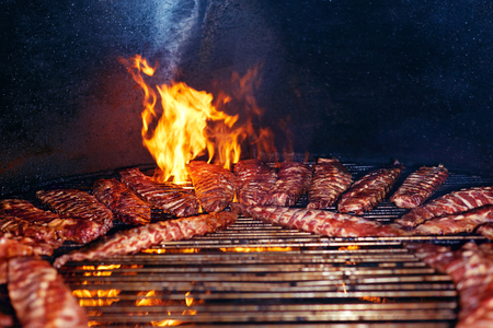 Pork Ribs Cooking On Grill Closeup. Cooking Grilling Meat On Fire. High Resolution