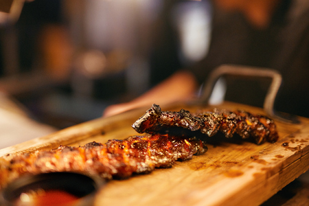 Barbecue Ribs With Sauce In Grill Bar. Spareribs On Wooden Tray In Restaurant Kitchen. High Resolution