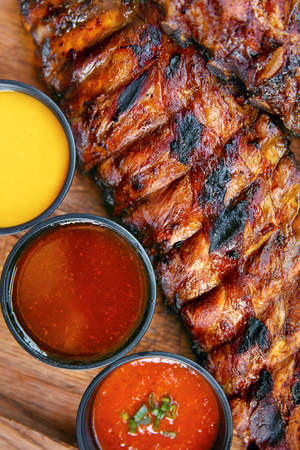 Barbecue Food. Grilled Meat With Sauce Close Up. Pork Ribs With Sauces In Restaurant. High Resolution