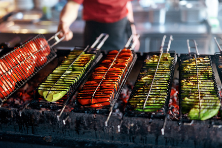 Vegetables On Barbecue Grill Closeup. Tomatoes And Zucchini Grilling On Skewers, Cooking On Heat. High Resolution