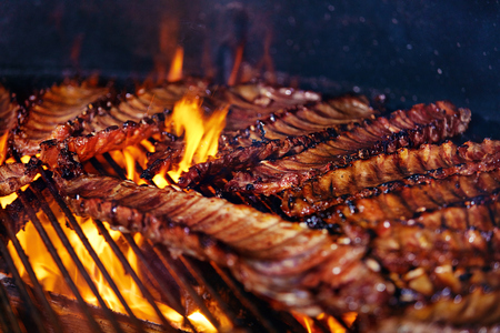Pork Ribs Cooking On Grill Closeup. Cooking Grilling Meat On Fire. High Resolution Banco de Imagens - 108465228