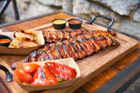 Food Closeup. Grilled Ribs In Barbecue Restaurant. Spareribs With Vegetables And Sauce On Wooden Tray. High Resolution
