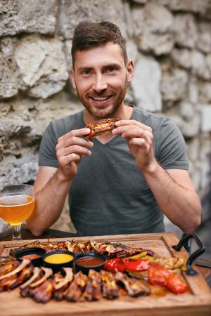 Man Eating Barbecue Meat With Beer. Handsome Man Having Dinner in Grill Restaurant. High Resolution Stock Photo