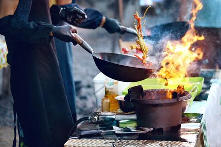 Cucinare il cibo in fiamme sul festival di strada. Chef Di Cucina Piatto Tailandese In Wok All'aperto. Alta risoluzione Archivio Fotografico - 108465302
