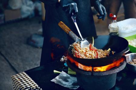 Koken eten in brand op straatfestival. Chef-kok Thaise Schotel In Wok Buiten Koken. Hoge resolutie