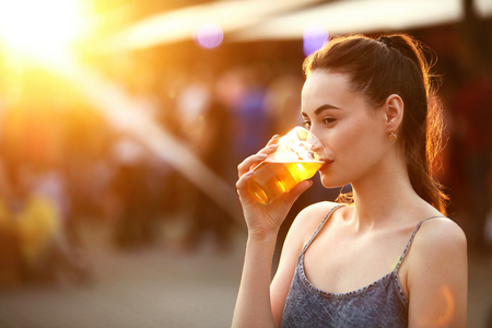 Woman Drinking Beer Outdoors. Attractive Girl With Beer Glass On Festival. High Resolution Stock Photo
