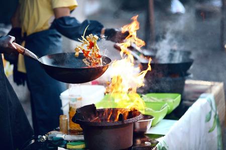 Kochen von Essen in Flammen auf dem Straßenfest. Chefkoch, der thailändisches Gericht im Wok im Freien kocht. Hohe Auflösung