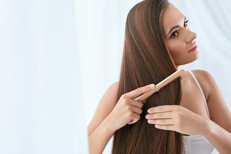 Haarpflege. Frau, die schöne lange Haare mit Holzbürste kämmt