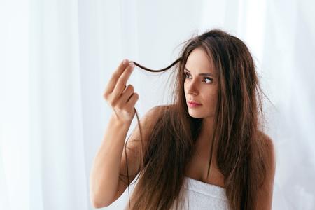 Problema del cabello. Mujer con cabello largo seco y dañado