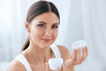 Hautpflege. Schöne Frau mit natürlicher Gesichtsschönheit, die Gesichtscreme in der Flasche im weißen Innenraum hält. Hohe Auflösung Standard-Bild